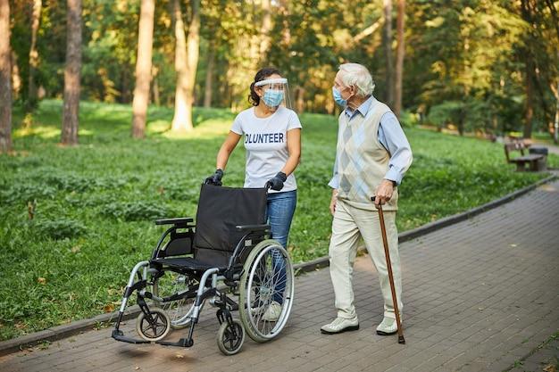 Mulher adulta alegre de camisa branca ajudando homem sênior