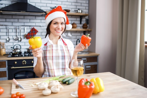 Mulher adulta alegre parada na cozinha e posando