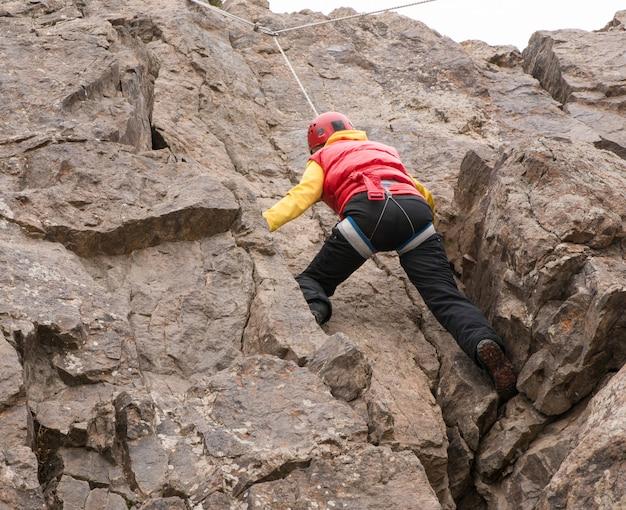 Mulher adulta alpinista escalando uma rocha. a temporada de inverno. vista de baixo