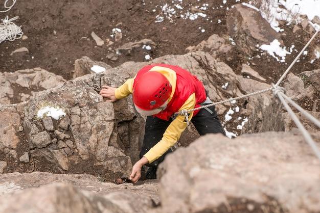 Mulher adulta alpinista escalando uma rocha. a temporada de inverno. vista do topo