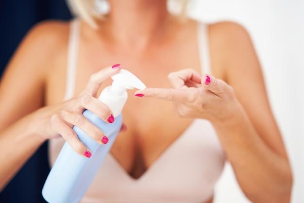 Mulher adulta aplicando hidratante corporal em casa