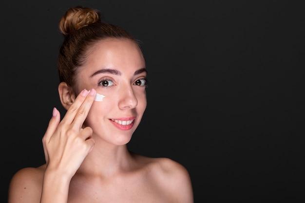 Mulher adulta, aplicar o produto de cuidados da pele