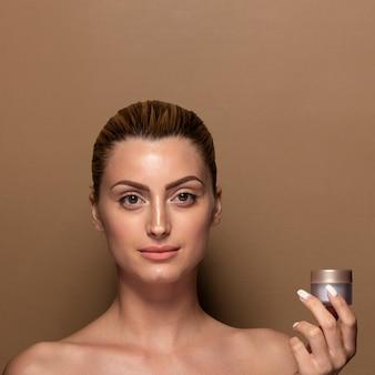 Mulher adulta, apresentando o produto de cuidados da pele