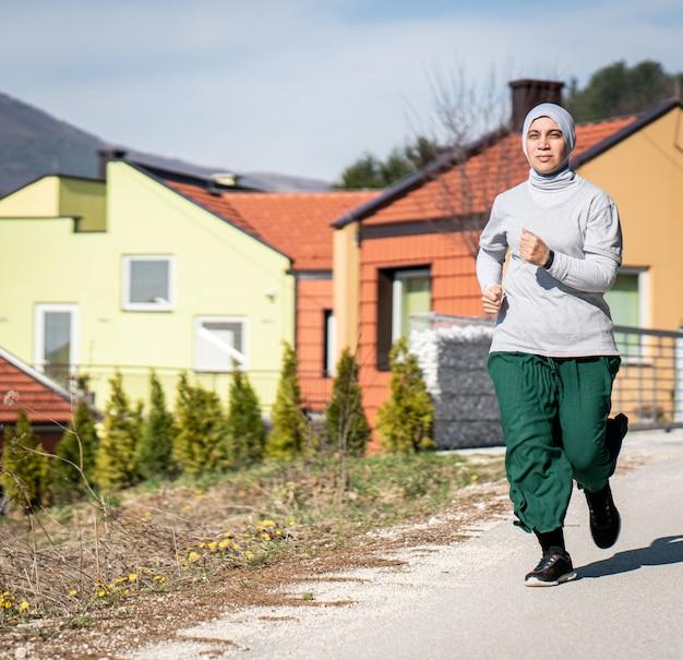 Mulher adulta árabe correndo na natureza