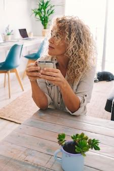 Mulher adulta atraente aproveitar o tempo e relaxar na atividade de lazer interna com sala de estar ao fundo. pessoas felizes do sexo feminino com cabelo loiro encaracolado e uma casa aconchegante na moda. senhora bonita e descontraída