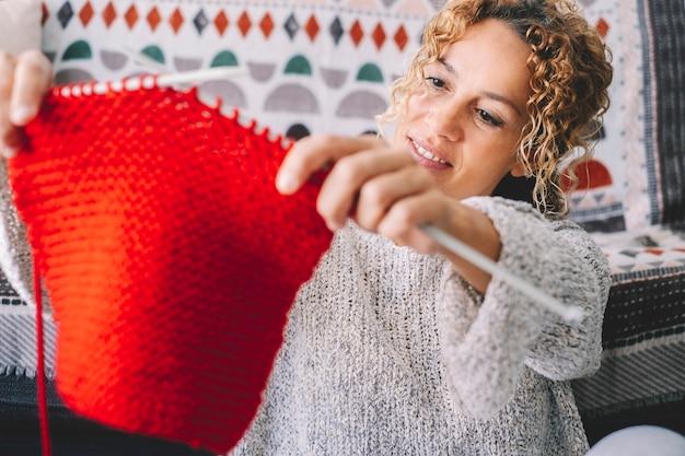 Mulher adulta atraente em casa na atividade de trabalho de tricô usando lã colorida. mulheres felizes e relaxadas, aproveitando o tempo interior no sofá. trabalho de tricô