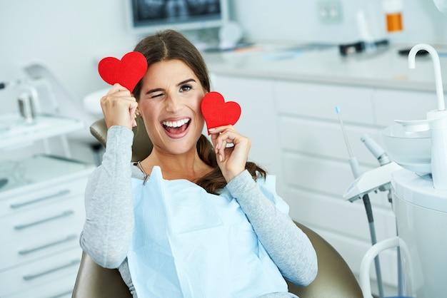 Mulher adulta atraente em consultório dentista com corações