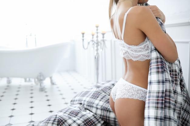 Mulher adulta atraente em lingerie branca erótica