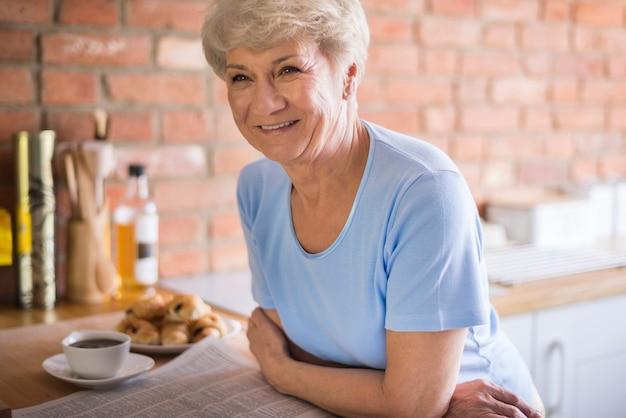 Mulher adulta atraente na cozinha doméstica