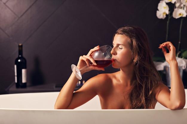 Mulher adulta atraente relaxando em uma banheira com lareira ao fundo