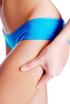 Mulher adulta beliscando a perna para teste de dobras cutâneas