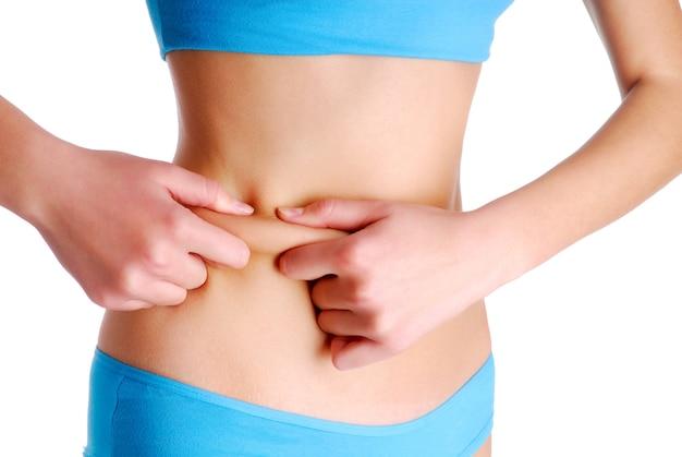 Mulher adulta beliscando pele na cintura para teste