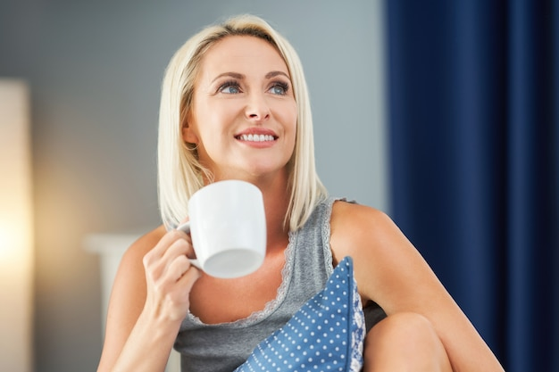 Mulher adulta bonita acordando totalmente descansada e bebendo café