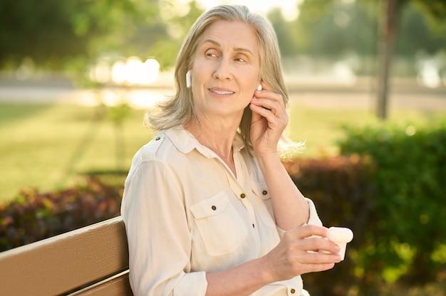 Mulher adulta bonita com fones de ouvido no banco