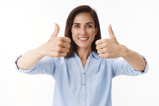 Mulher adulta bonita de apoio com tatuagens, empreendedora dando sinal de aprovação com o polegar para cima, sorrindo, entretida, encantada por ouvir um bom conceito, aceitar os termos