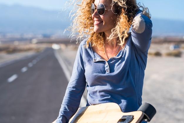 Mulher adulta bonita e atraente alegre sorria e desfruta da liberdade usando uma longa mesa de skate com a estrada no fundo