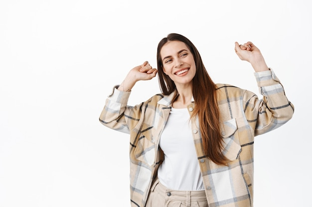 Mulher adulta bonita em camisa xadrez se divertindo, dançando e comemorando, sorrindo e parecendo despreocupada, relaxando na pista de dança, em pé sobre uma parede branca