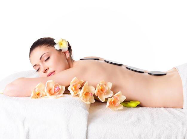 Mulher adulta bonita relaxando em um salão de spa com pedras quentes nas costas