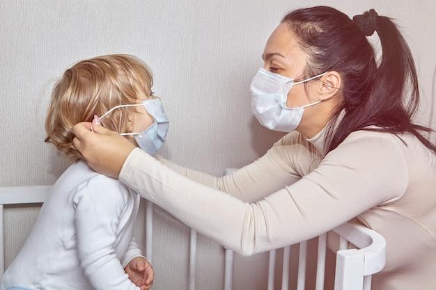 Mulher adulta branca branca com máscara médica no rosto está colocando a mesma máscara em sua filha como proteção contra poluição do ar ou gripe.