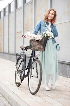 Mulher adulta caminhando com bicicleta urbana