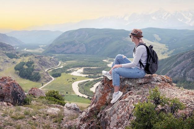 Mulher adulta caminhante senta-se e pensando, olhando para o pôr do sol.