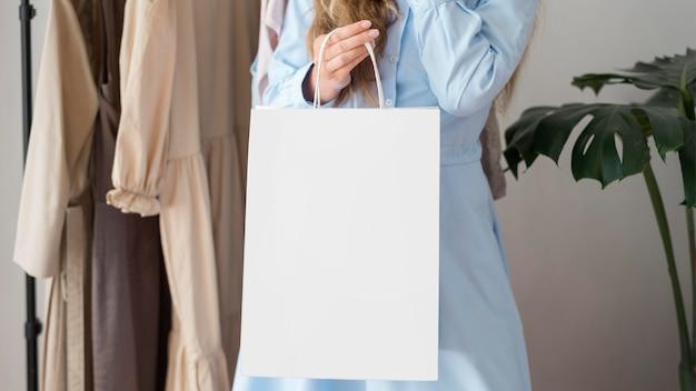Mulher adulta carregando sacola de compras