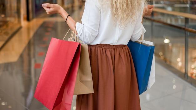 Mulher adulta carregando sacolas de compras no shopping