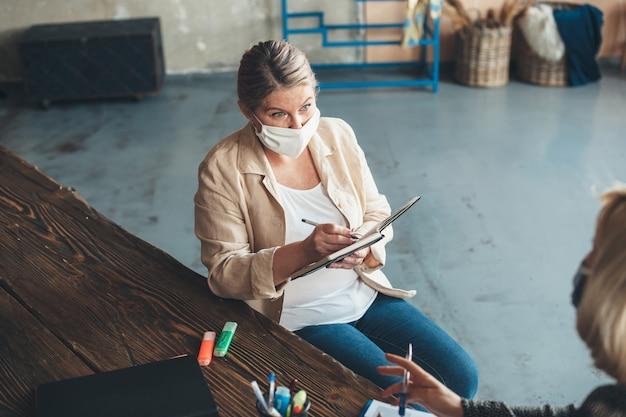 Mulher adulta caucasiana com máscara médica no rosto está trabalhando em casa com um cliente