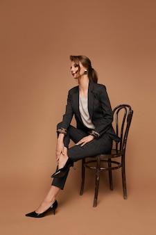 Mulher adulta caucasiana de negócios, com uma blusa de terno cinza e sapatos pretos, posando na cadeira sobre uma parede bege isolada com espaço de cópia