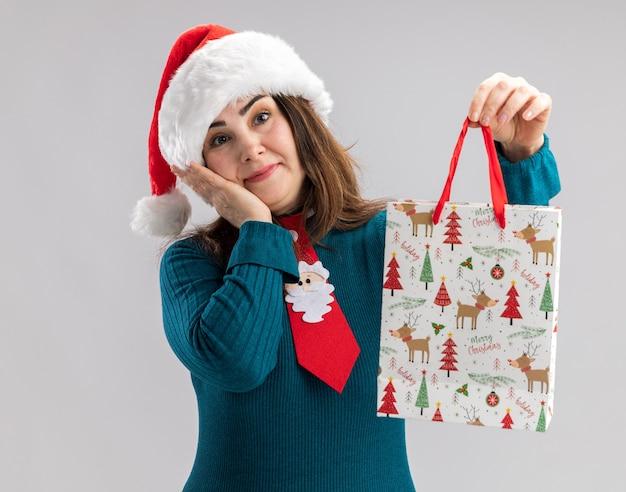 Mulher adulta caucasiana feliz com chapéu de papai noel e gravata de papai noel coloca a mão no rosto e segura uma caixa de presente de papel isolada na parede branca com espaço de cópia
