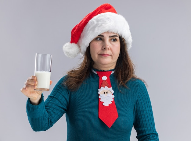 Mulher adulta caucasiana feliz com chapéu de papai noel e gravata de papai noel segurando um copo de leite, olhando para o lado isolado na parede branca com espaço de cópia