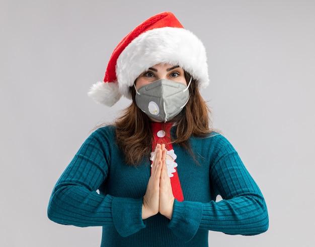 Mulher adulta caucasiana feliz com chapéu de papai noel e gravata de papai noel usando máscara médica de mãos dadas, isolados na parede branca com espaço de cópia