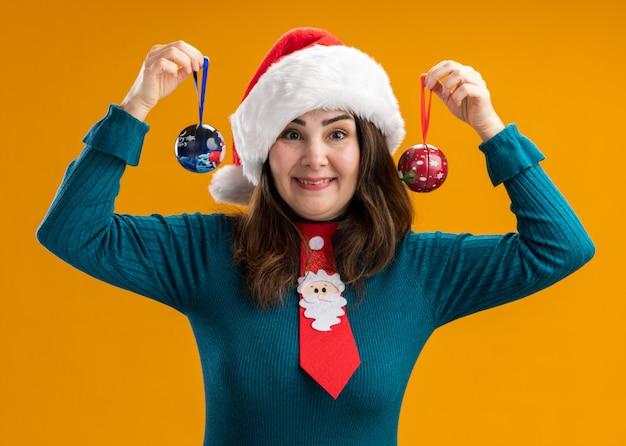 Mulher adulta caucasiana impressionada com chapéu de papai noel e gravata de papai noel segurando enfeites de bola de vidro isolados na parede laranja com espaço de cópia
