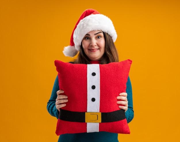 Mulher adulta caucasiana impressionada com chapéu de papai noel e gravata de papai noel segurando uma almofada decorada isolada na parede laranja com espaço de cópia