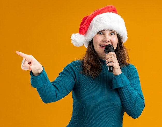 Mulher adulta caucasiana impressionada com chapéu de papai noel segurando o microfone e apontando para o lado isolado em um fundo laranja com espaço de cópia