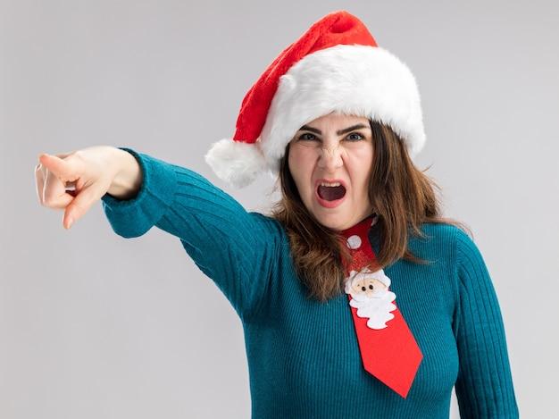 Mulher adulta caucasiana irritada com chapéu de papai noel e gravata de papai noel apontando para o lado isolado na parede branca com espaço de cópia