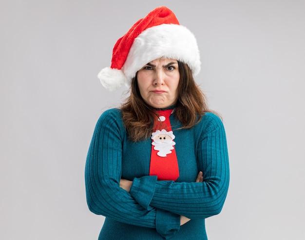 Mulher adulta caucasiana irritada com chapéu de papai noel e gravata de papai noel em pé com os braços cruzados, isolado na parede branca com espaço de cópia