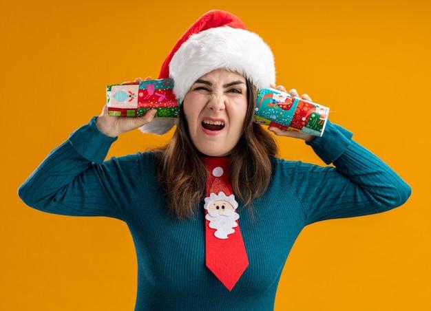 Mulher adulta caucasiana irritada com chapéu de papai noel e gravata de papai noel segurando copos de papel perto das orelhas, isolados em um fundo laranja com espaço de cópia