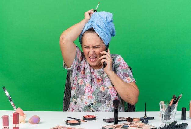 Mulher adulta caucasiana irritada com o cabelo enrolado em uma toalha, sentada à mesa com ferramentas de maquiagem, falando no telefone e segurando brilho labial isolado na parede verde com espaço de cópia
