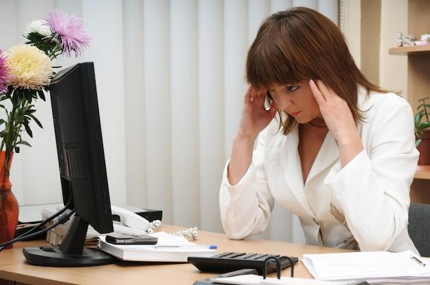 Mulher adulta caucasiana morena branca intrigada, sentado e segurando a cabeça pensando na tarefa acima da mesa.