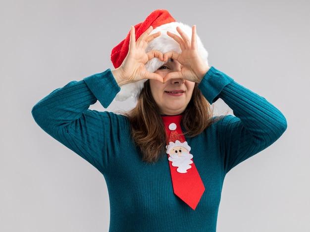 Mulher adulta caucasiana satisfeita com chapéu de papai noel e gravata de papai noel gesticulando e através do sinal de coração isolado na parede branca com espaço de cópia