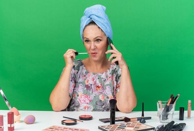 Mulher adulta caucasiana satisfeita com o cabelo enrolado em uma toalha, sentada à mesa com ferramentas de maquiagem, falando ao telefone e aplicando brilho labial