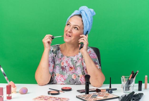 Mulher adulta caucasiana satisfeita com o cabelo enrolado em uma toalha, sentada à mesa com ferramentas de maquiagem, falando no telefone e segurando brilho labial, olhando para o lado