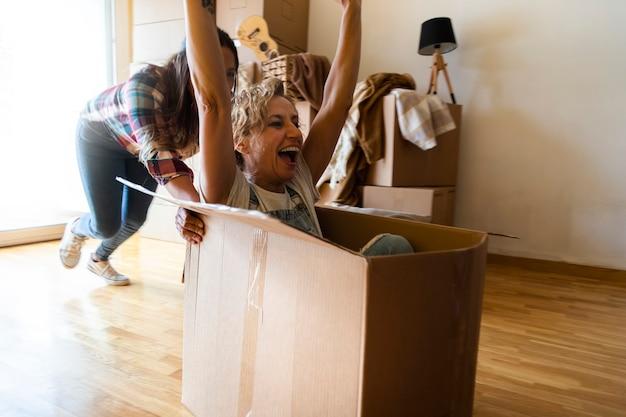 Mulher adulta caucasiana se divertindo com caixas de papelão movendo-se mulher madura rindo relocação