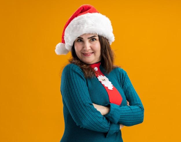 Mulher adulta caucasiana sorridente com chapéu de papai noel e gravata de papai noel fica com os braços cruzados isolados na parede laranja com espaço de cópia