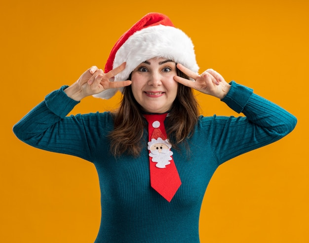 Mulher adulta caucasiana sorridente com chapéu de papai noel e gravata de papai noel gesticulando o sinal da vitória através dos dedos isolados na parede laranja com espaço de cópia