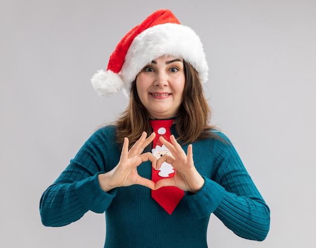 Mulher adulta caucasiana sorridente com chapéu de papai noel e gravata de papai noel gesticulando sinal de coração isolado na parede branca com espaço de cópia
