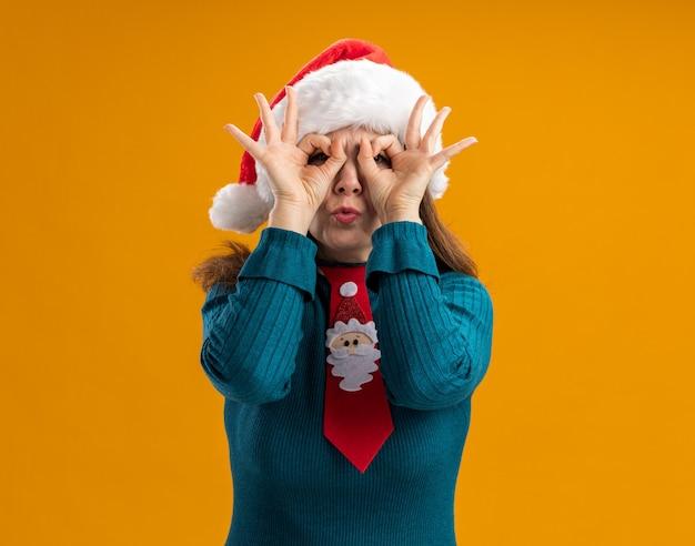 Mulher adulta caucasiana surpreendida com chapéu de papai noel e gravata de papai noel através de dedos isolados em uma parede laranja com espaço de cópia