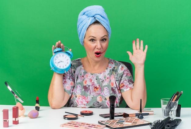 Mulher adulta caucasiana surpresa com o cabelo enrolado em uma toalha, sentada à mesa com ferramentas de maquiagem, segurando o despertador e mantendo a mão aberta