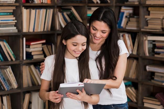 Mulher adulta close-up, e, menina jovem, leitura